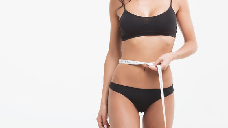 Woman in black bra and underwear holding measuring tape around fit torso